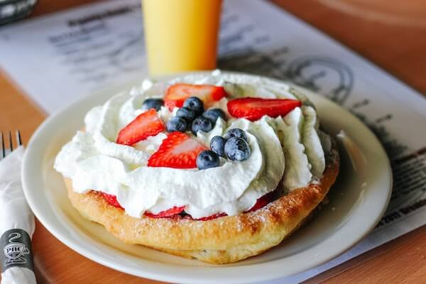 Scone topped with whipped cream and fruit